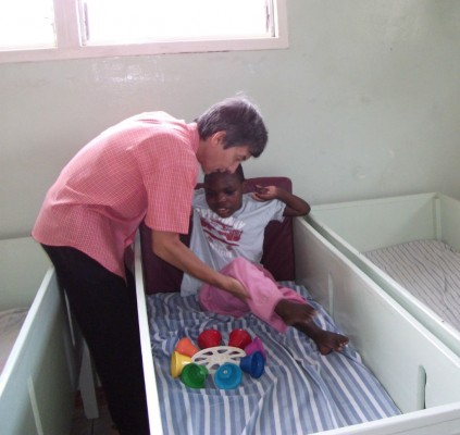 A Physical Therapist works with a Special Needs Girl
